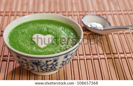 chilled sweet pea soup garnished with a heart shaped cream drop served on a bamboo place mat