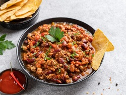 Chilli con carne in black ceramic plate with tortilla corn chips (nachos) and red spicy sauce. Close up view, copy space. Traditional mexican dish, stewed minced meat with red beans and vegetables.