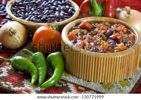 Chilli con carne in wooden bowl and different vegetables