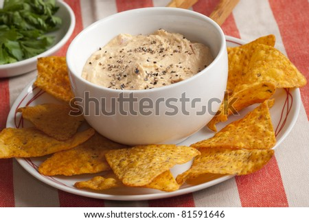 Chilli crisps with roasted red pepper houmous on a plate