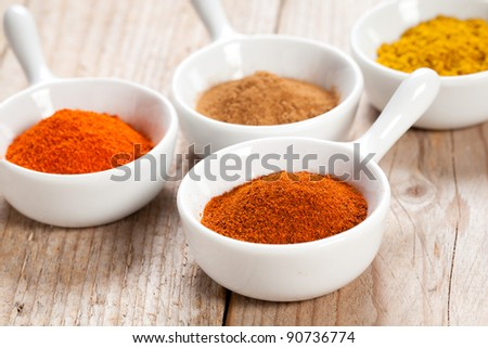 Chilli pepper and assorted spicy powders in white bowls over a wooden table