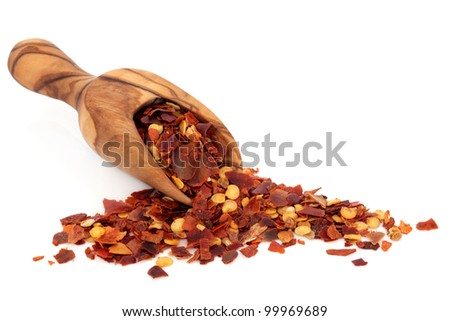 Chilli spice flakes in an olive wood scoop and scattered over white background. - stock photo