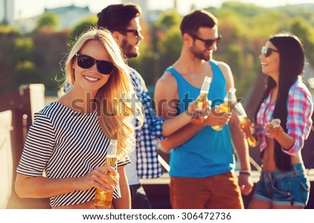 Chilling out with friends. Smiling young woman holding bottle of beer and looking at camera while three people talking to each other in the background #306472736
