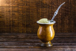 Chimarrão, or mate herb, is a South American drink left by indigenous cultures. It consists of a gourd, a pump, ground yerba mate and boiling water. Chimarrão isolated on wooden background. Copy space