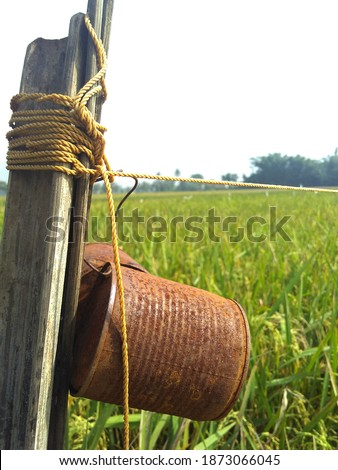 chime bells made out of recycled rustic tin cans hanged with ropes on a bamboo pole to scare birds away on a rice field in Kepanjen village, Malang, East Java, Indonesia ストックフォト ©