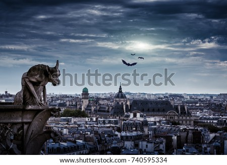 Chimera (gargoyle) of the Cathedral of Notre Dame de Paris overlooking Paris on Halloween, France. Paris skyline at night. Aerial mystic view of Paris at dusk. Panorama of the old city in moonlight.