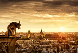 Chimera or gargoyle on the Cathedral of Notre Dame de Paris overlooking Paris at sunset, France. Panorama of Paris with the evil statue in sunlight. Beautiful sunny view of Paris under dramatic sky.