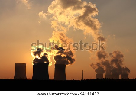 chimney and cooling towers of power plant during sunset