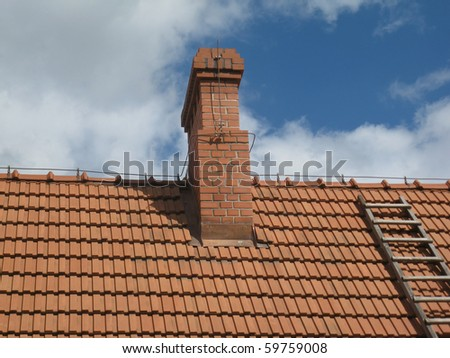 chimney and part of the roof with a ladder and a cloudless sky