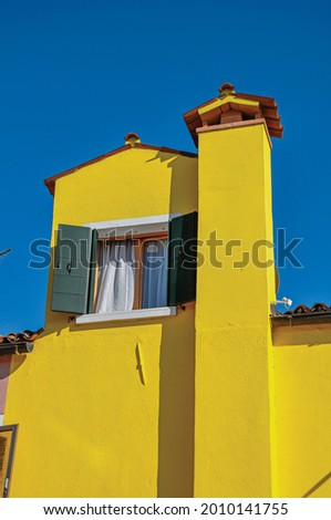 Chimney and window with open blinds in a colorful house on sunny day in Burano, a gracious little town full of canals near Venice. Northern Italy. Stock fotó ©