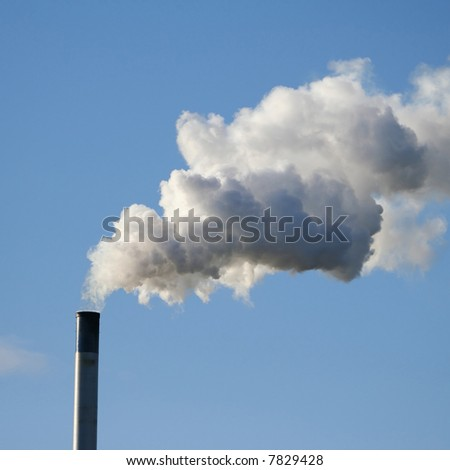 chimney billowing white smoke into blue sky