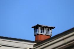 Chimney cap topper on house roof terra cotta liner blue sky