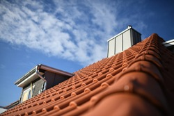 chimney on roof with new red roofing tiles on residential property. banner on the roof for roofers with beautiful sky