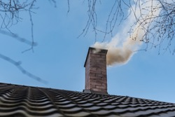 Chimney on the roof of a detached house. The smoke from the chimney. House heating, beginning of the heating season. Burning coal and wood in the furnace. Air pollution and smog in the winter season.