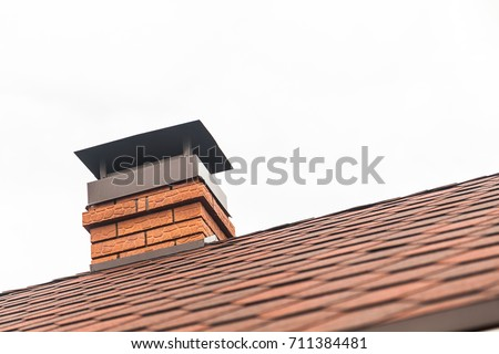 Chimney pipe in red bricks on roof in red shingles. On white background