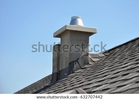 Chimney Repair and Waterproofing asphalt shingles. New modular pumice chimney installation on the house roof. Chimney Linings. Pumice chimney liners.