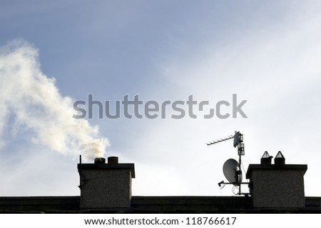 chimney stacks on estate house with smoke rising on a winters evening