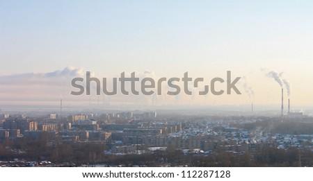 Chimney-stalks pollute atmosphere. Smoke on the city.