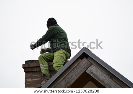 Chimney sweep man cleaning brown brick chimney on building roof on clear sky background with copy space for text.