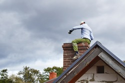 Chimney sweep man cleaning brown brick chimney while sitting on chimney on building roof on cloudy sky background with copy space for text. DIY concept.