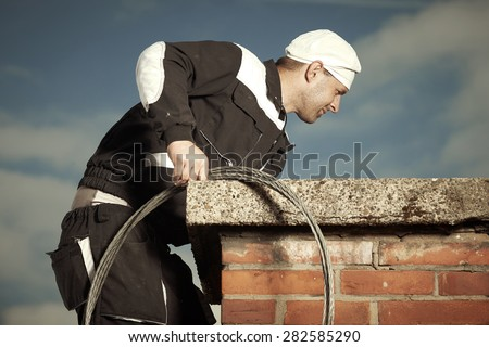 Chimney sweep man in work uniform cleaning chimney on building roof