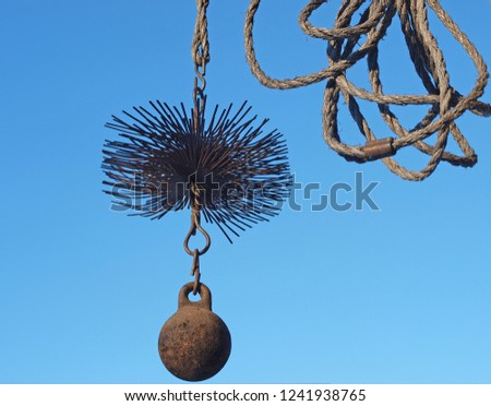 Chimney sweeper tools close up metal wire brush with weight and rope on blue sky background