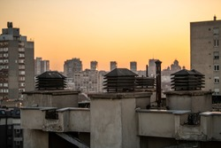 Chimney system on flat rooftop of residential building, with cityscape in background at sunset. Ventilation chimney with a rain cap and shielding. Smokestack pipes.