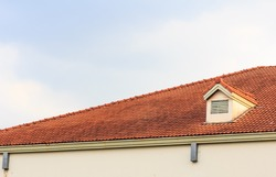 Chimneys on roof of red tiles with blue sky and clouds.