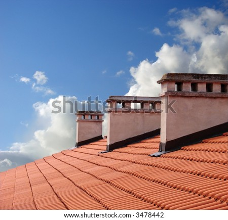 Chimneys on roof of red tiles with blue sky and clouds. - stock photo