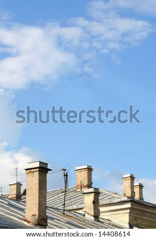 Chimneys on roofs with blue sky and clouds