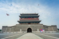 China ancient big city gate with kites flying in the blue cloudy sky
