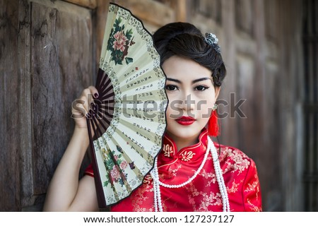 China Girl,Chinese woman red dress traditional cheongsam ,close up portrait with old wood door
