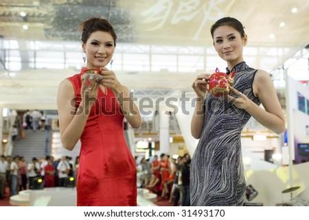 CHINA, GUANGDONG, SHENZHEN - MAY 16: China Cultural Industries Fair: beautiful Chinese hostess present Chinese porcelain, ceramic tea sets, vases, pots, plates in Guangdong, Shenzhen, China on May16, 2009
