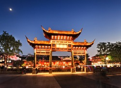 China Nanjing city area around confucius temple with wooden historic gate and background red wall with fire dragons illuminated at sunset