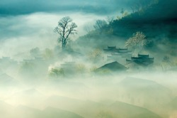 China Old City Town Anhui Landscape. Ancient Traditional Chinese Architecture Houses in Fog View. Peaceful Green Trees and Small Rural Village. Rustic Background Image.
