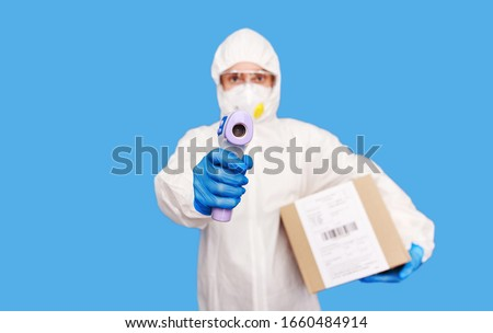 China post concept. Professional doctor in protective suit, glasses and face mask standing isolated on blue background, holding package box in hands. Europe is afraid of infections through the premis. Foto stock ©