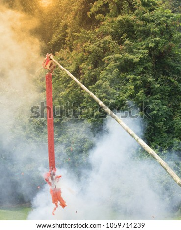 China red cracker line hanging on bamboo stick are fired and continue to explode in Chinese New Year Event. #1059714239