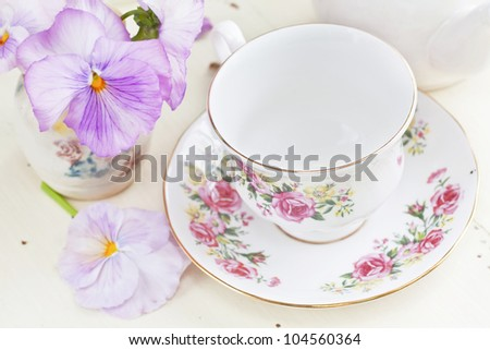 China teacup and pink springtime pansies by a morning window.