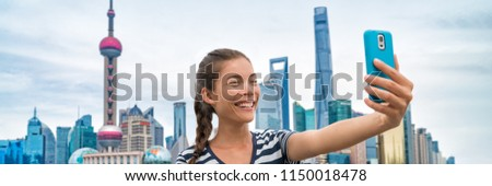 China travel Asian girl tourist taking phone selfie photo on the Bund in Shanghai city vacation. Happy chinese young woman using smartphone app vlogging posting on social media. Multiracial person. #1150018478