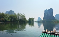 China. Yangshuo. Beautiful unusual tranquil landscape with green karst hills on the Li River. Bamboo tourist raft for a river walk. Natural background