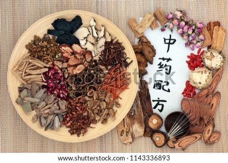 Chinese acupuncture needles with traditional herbs used in herbal medicine with calligraphy script on bamboo background. Translation reads as chinese alternative medicine. Top view.