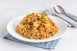 Chinese Asian Egg and Vegetable Fried Rice on a White Plate on the White Background.