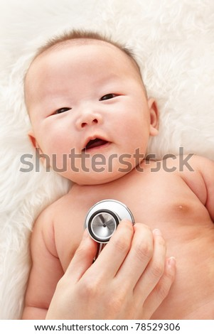 Chinese baby boy being examined by pediatrician on fur bed