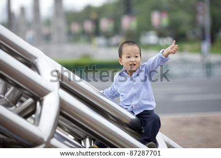 chinese baby boy climb the iron ladder outside