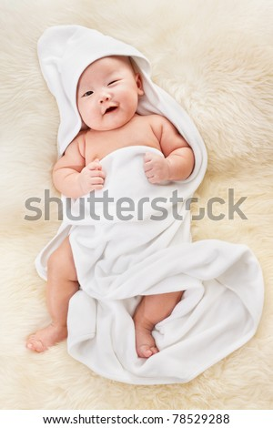 Chinese baby boy covered with white blanket on fur bed
