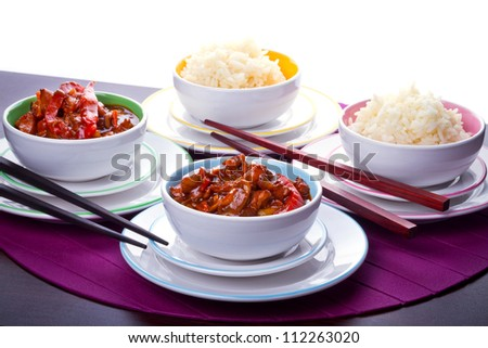 Chinese bowls with rice and sweet and sour chicken and chopsticks