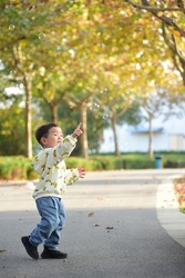 Chinese boy chasing bubbles and playing