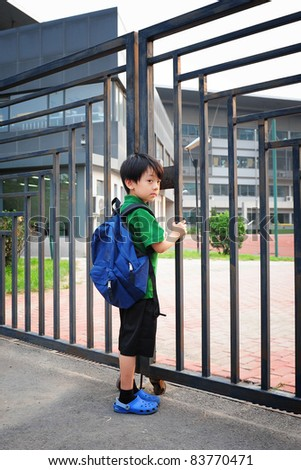 Chinese boy waiting in front of schoolgate