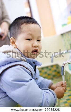 Chinese boy washing the hands beside the tank