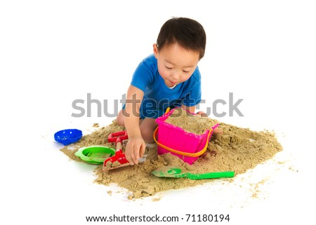 Chinese boy with sand playing at the beach isolated over white